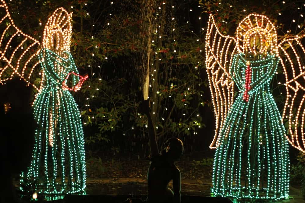 Two angels made of Christmas lights and a fountain