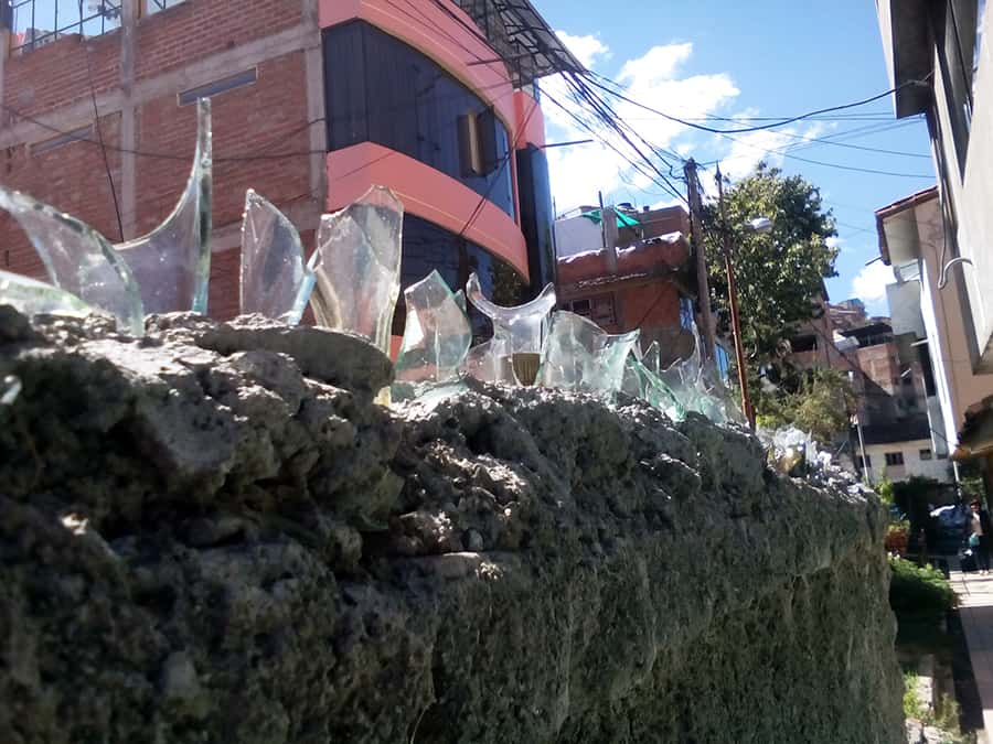 Yes, that is straight up broken glass bottles jutting out of the top of a fence. Don't try to jump fences in Peru--they will SHANK you.