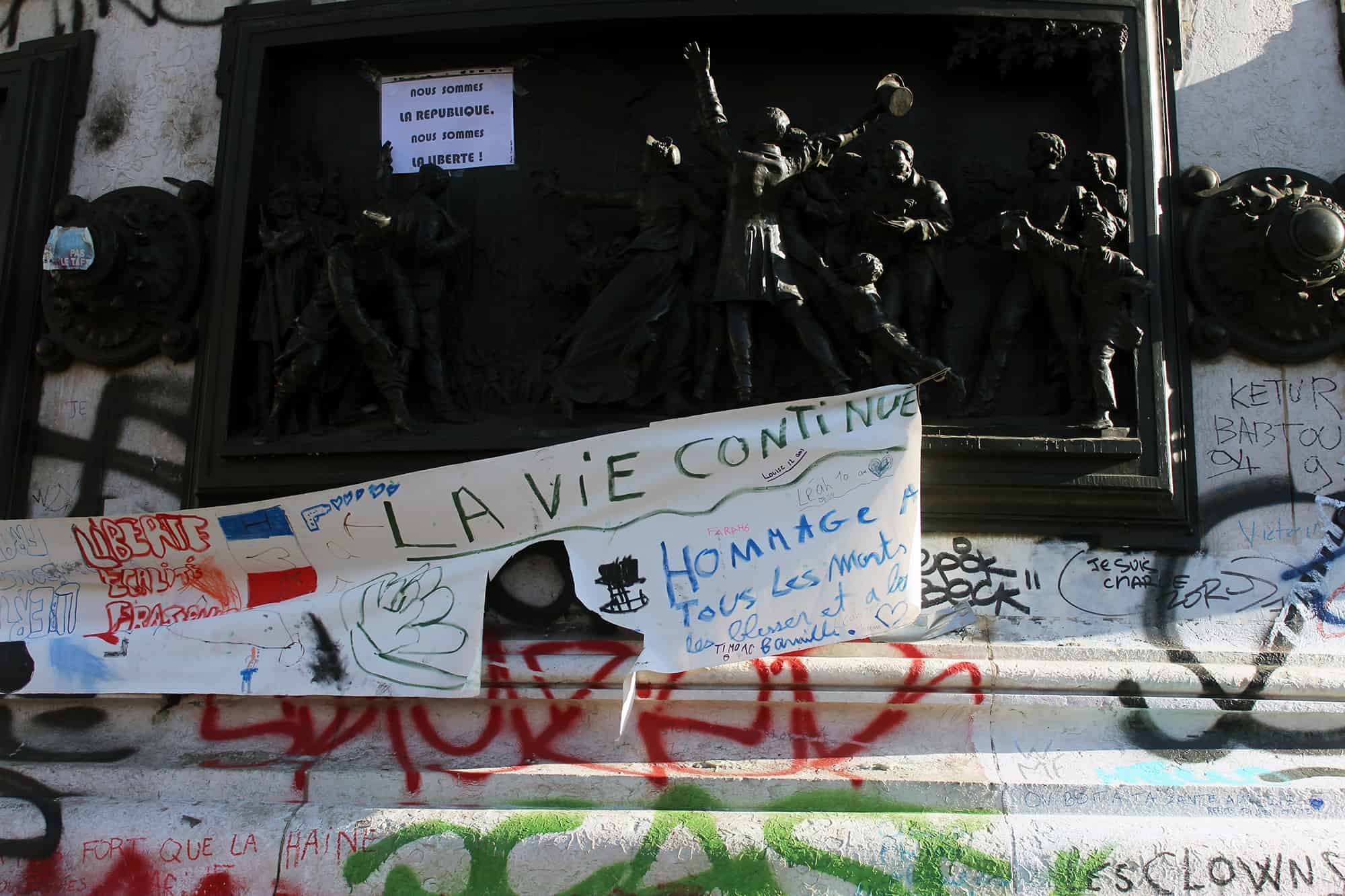 """Life goes on"" reads a sign hung on the monument at the Place de la Republique in Paris"